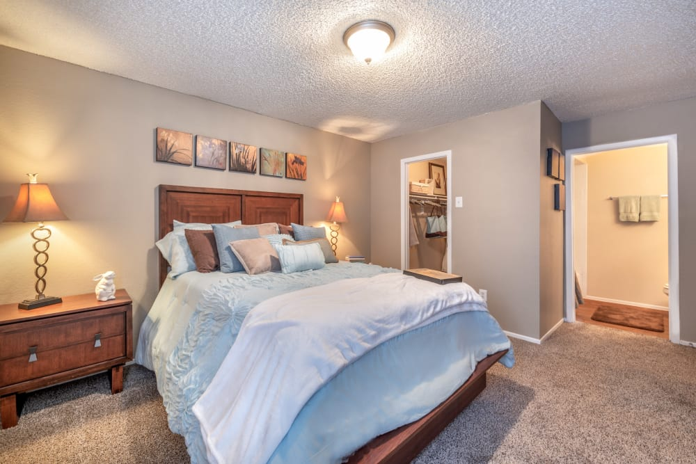 Bedroom with a walk-in closet and private bathroom at 8500 Harwood Apartment Homes in North Richland Hills, Texas