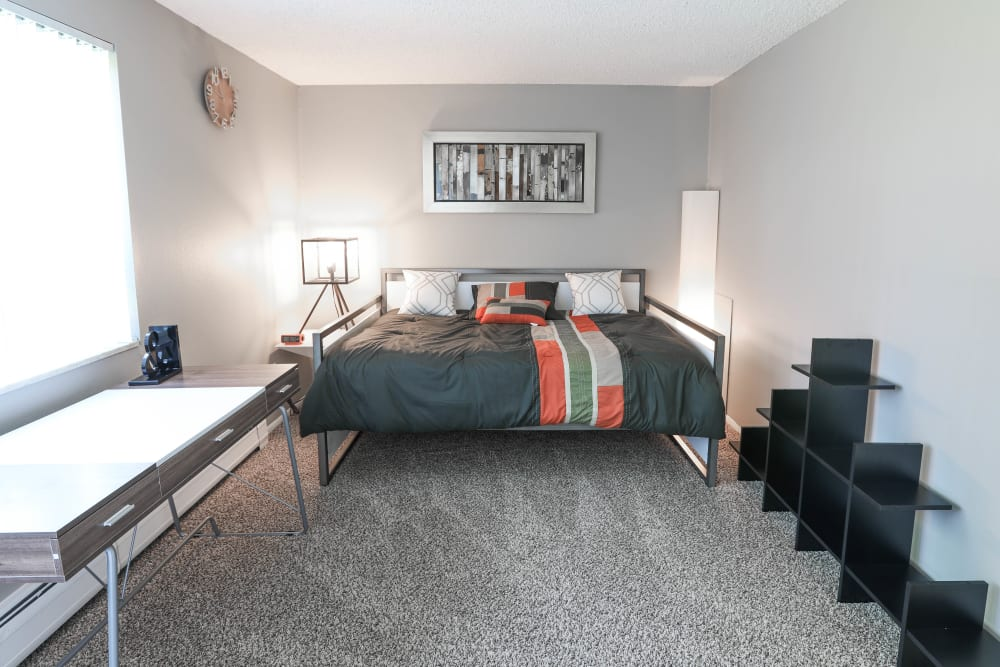 Master bedroom with large bay windows and plush carpeting in a model home at Ten49 in Broomfield, Colorado