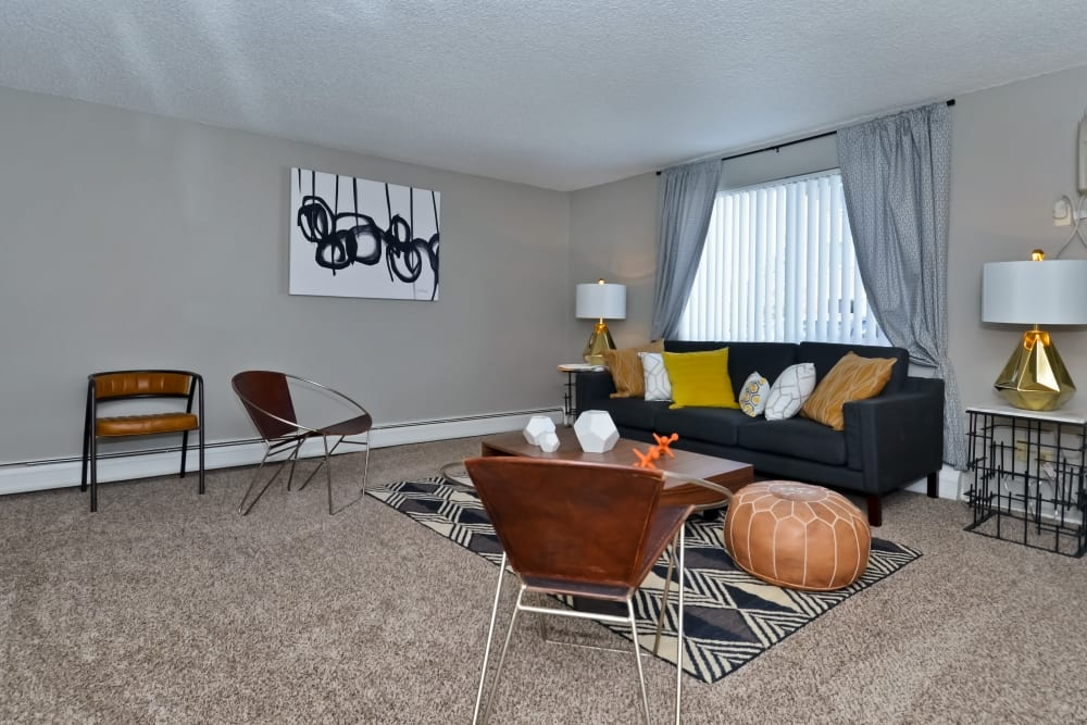 Draped windows and plush carpeting in the living area of a model home at Ten49 in Broomfield, Colorado