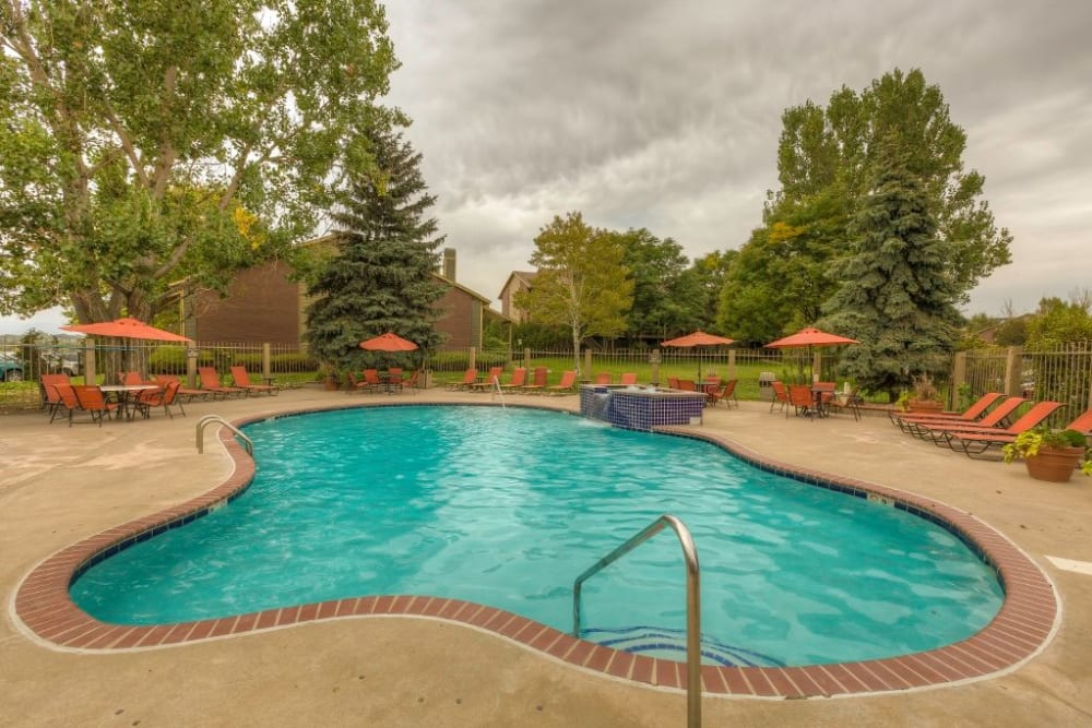 Resort-style swimming pool with chaise lounge chairs nearby at Skyline in Thornton, Colorado
