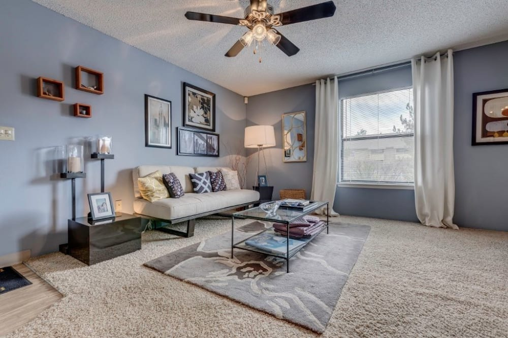 Modern furnishings and a ceiling fan in a model home's living space at Skyline in Thornton, Colorado