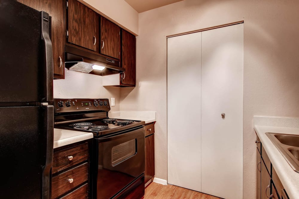 Resident kitchen with black appliances at Arvada Village Apartment Homes in Arvada, Colorado