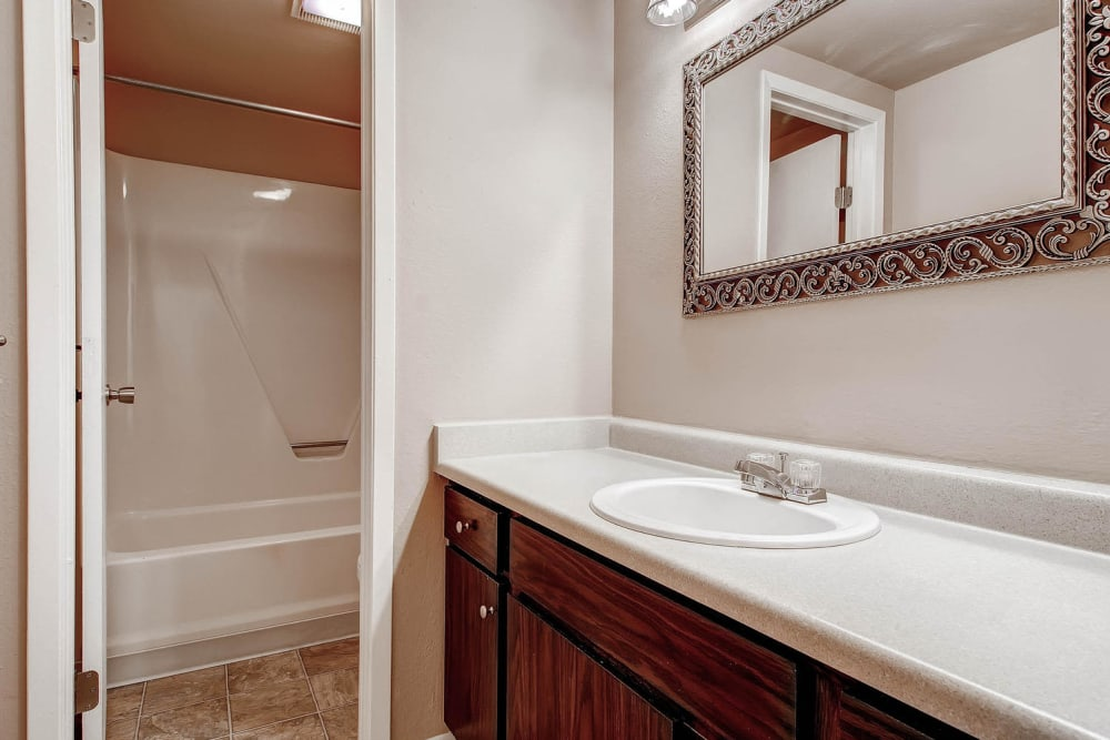 Resident bathroom with counter and storage space at Arvada Village Apartment Homes in Arvada, Colorado