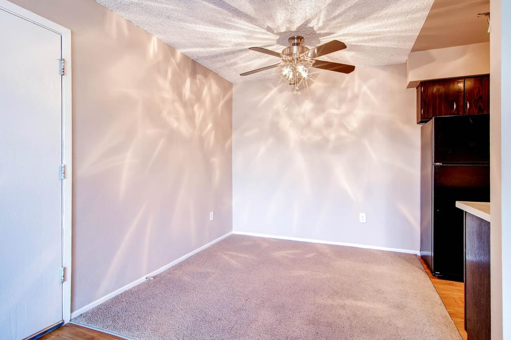 Model dining room with ceiling fan at Arvada Village Apartment Homes in Arvada, Colorado