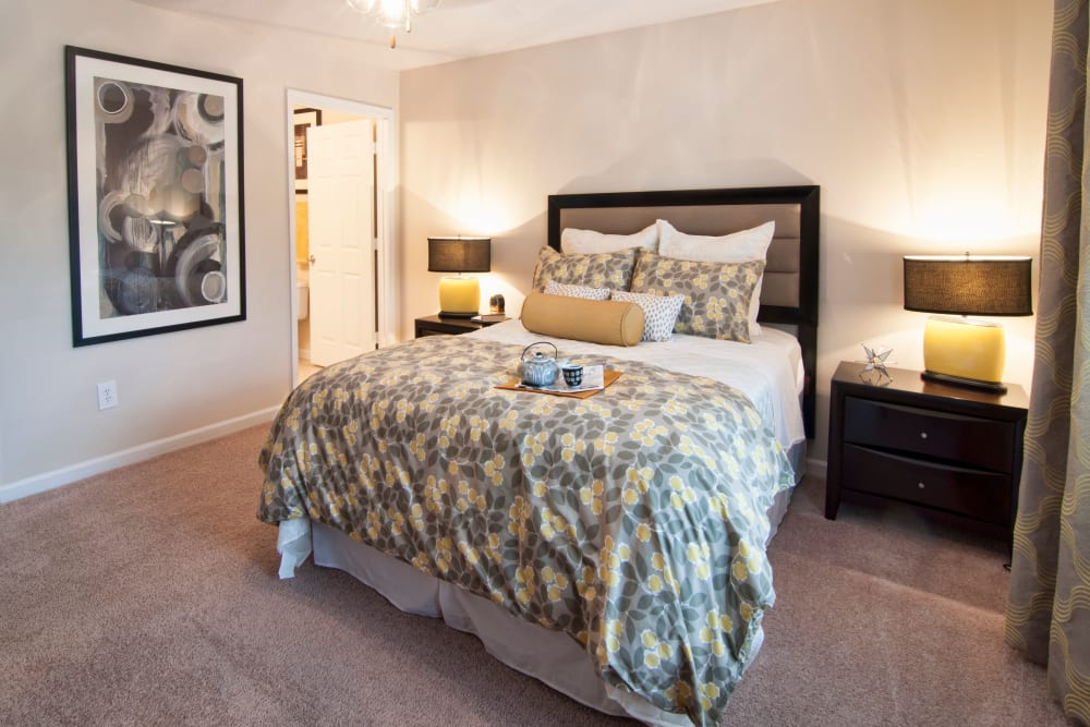 Master bedroom with an en suite bathroom in a model home at Bellingham Apartment Homes in Marietta, Georgia