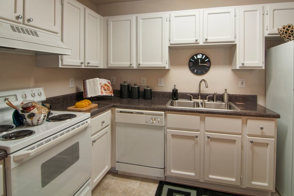 Modern kitchen with granite countertops and ample cupboard space in a model home at Bellingham Apartment Homes in Marietta, Georgia