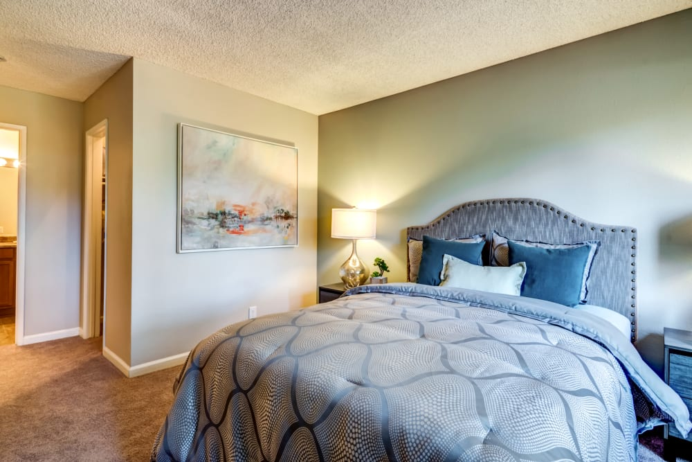 Well-furnished master bedroom with an en suite bathroom in a model home at Sofi Poway in Poway, California
