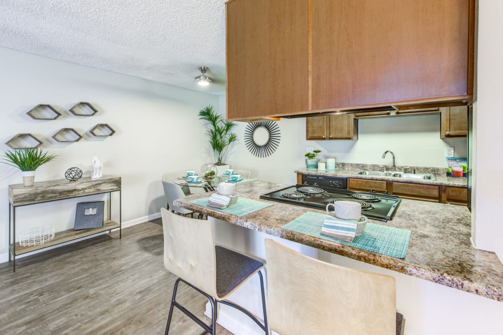 Kitchen with a breakfast bar and granite countertops in a model home at Sofi Poway in Poway, California