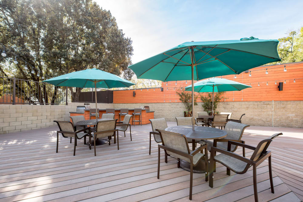 Umbrellas providing shade to tables and chairs at one of the outdoor common areas at Sofi Thousand Oaks in Thousand Oaks, California