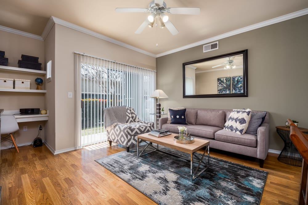 Hardwood flooring and a ceiling fan in the open-concept living area of a model home at Vail Quarters in Dallas, Texas