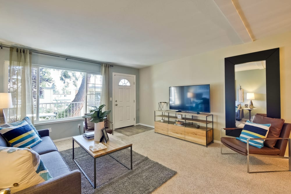 Large bay windows and plush carpeting in a model home's living space at Sofi at Los Gatos Creek in San Jose, California