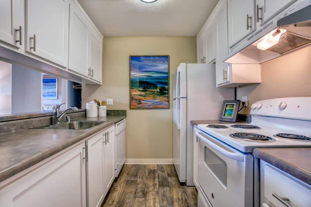 Modern kitchen with granite countertops and ample cupboard space in a model home at Sofi at Los Gatos Creek in San Jose, California