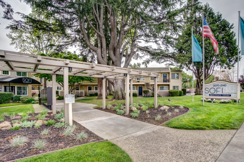 Pergola and well-maintained landscaping leading up to the leasing center at Sofi at Los Gatos Creek in San Jose, California