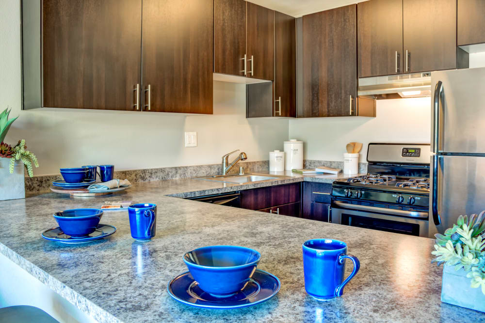 Gourmet kitchen with expansive granite countertops in a model home at Sofi Belmont Hills in Belmont, California