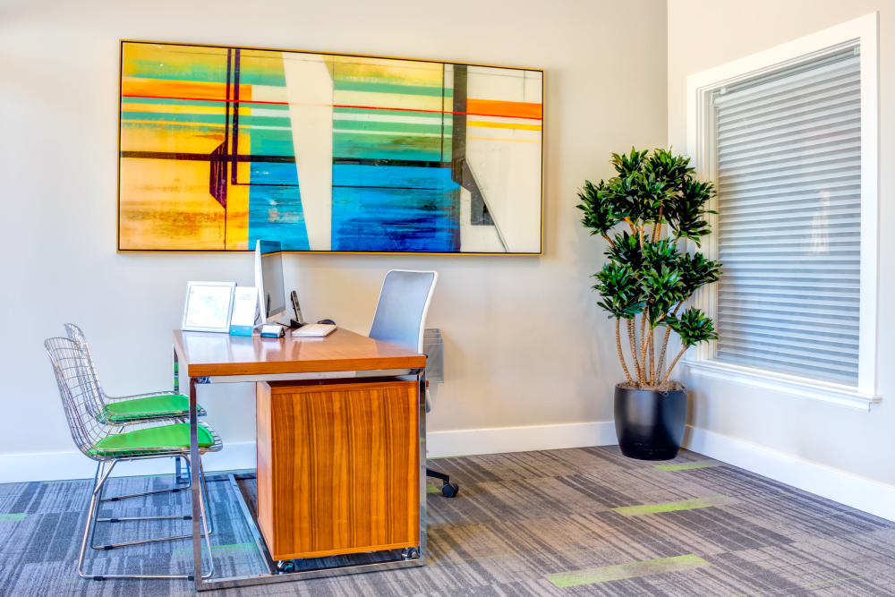 Leasing desk with colorful art on the wall nearby at Sofi Belmont Hills in Belmont, California