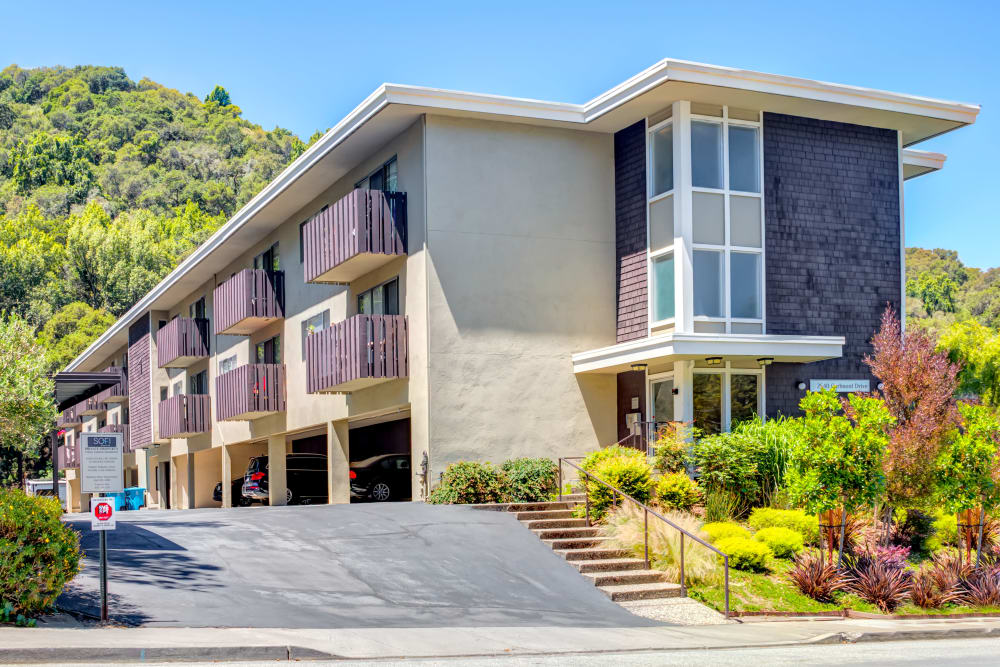 Exterior view of the resident building with covered parking underneath at Sofi Belmont Hills in Belmont, California