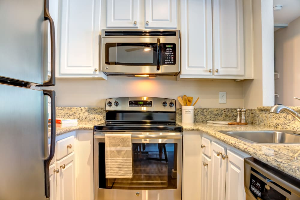 Gourmet kitchen with granite countertops and ample cupboard space in a model home at Sofi Berryessa in San Jose, California