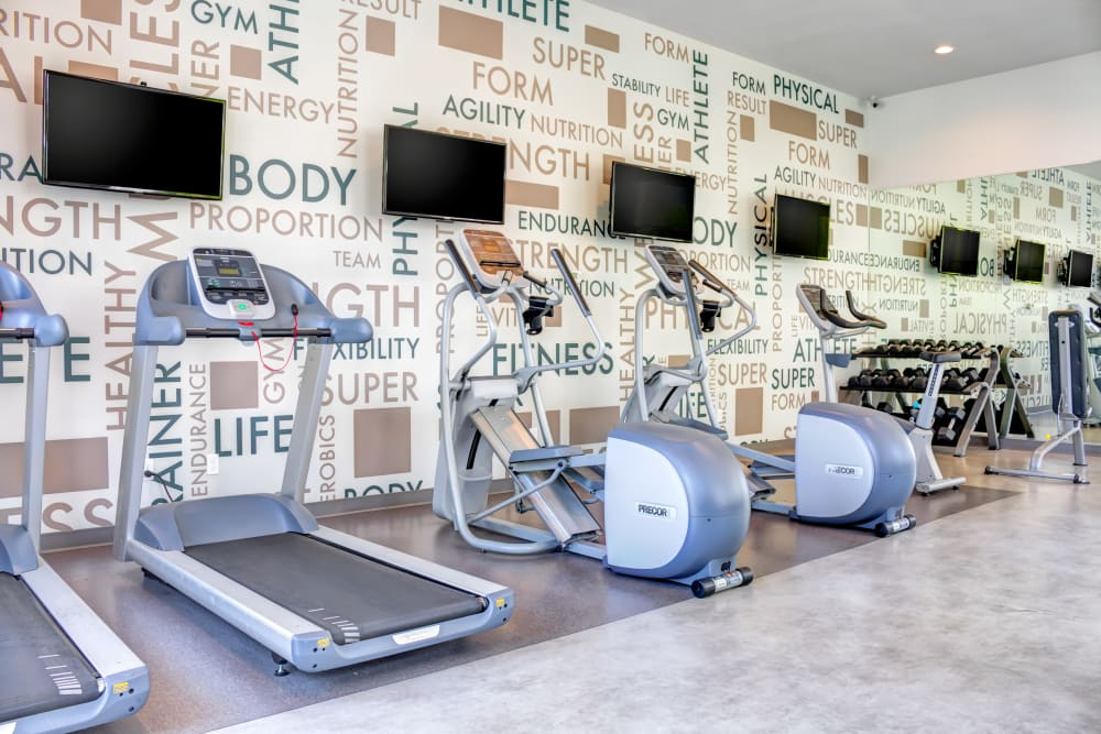 Well-equipped onsite fitness center with motivational wallpaper at Sofi Berryessa in San Jose, California