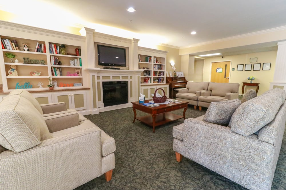 A reading room with bookcases, a television and a fireplace at The Crossings at Bon Air in Richmond, Virginia