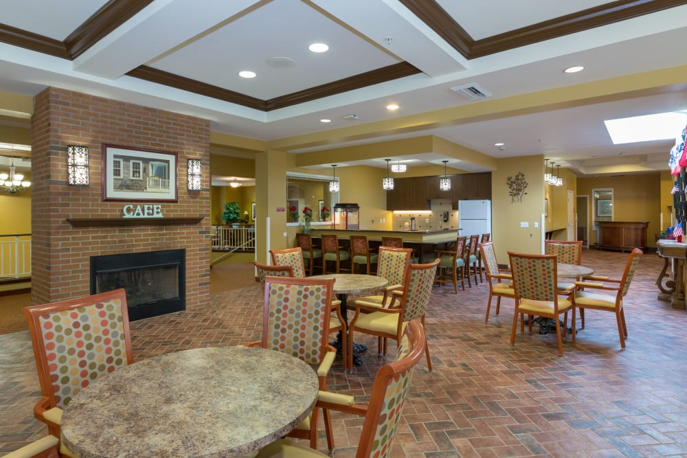 A community area with tables, chairs and a fireplace at The Reserve at East Longmeadow in East Longmeadow, Massachusetts
