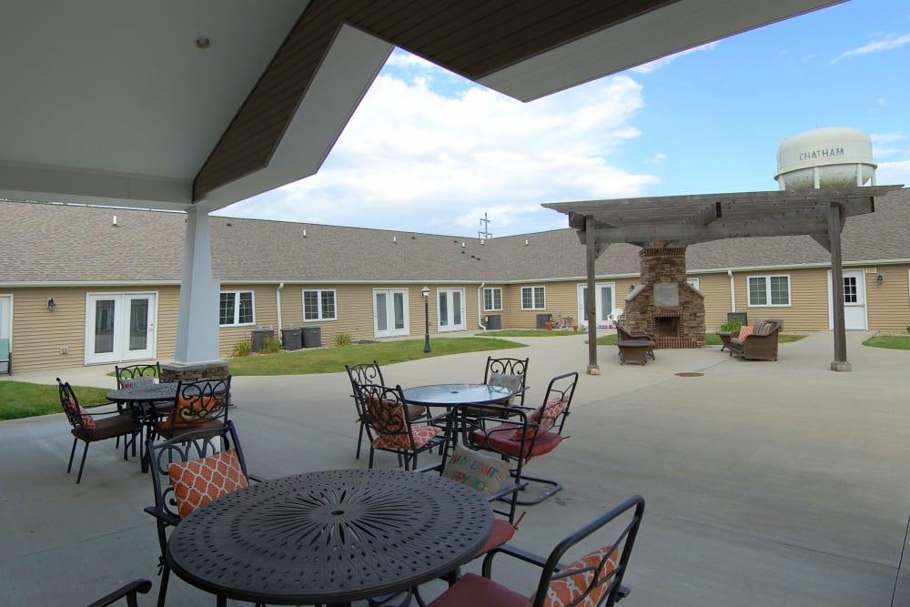 Concrete covered patio with tables and chairs at Villas of Holly Brook Chatham in Chatham, Illinois