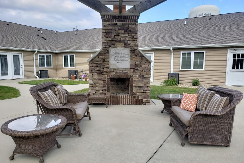 Outdoor seating by a fireplace at Villas of Holly Brook Chatham in Chatham, Illinois