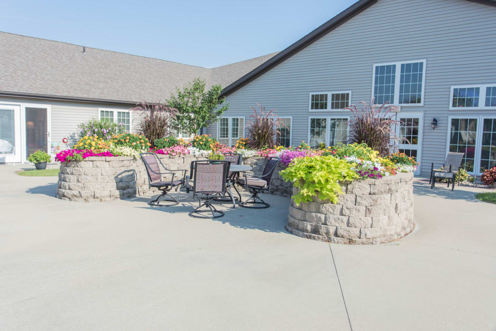 Outdoor concrete courtyard with planters and lots of seating at Villas of Holly Brook Effingham in Effingham, Illinois