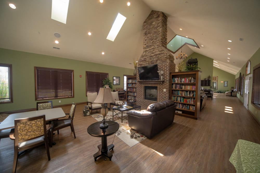community lounge area with a fireplace, couch, and books at Villas of Holly Brook Herrin in Carterville, Illinois