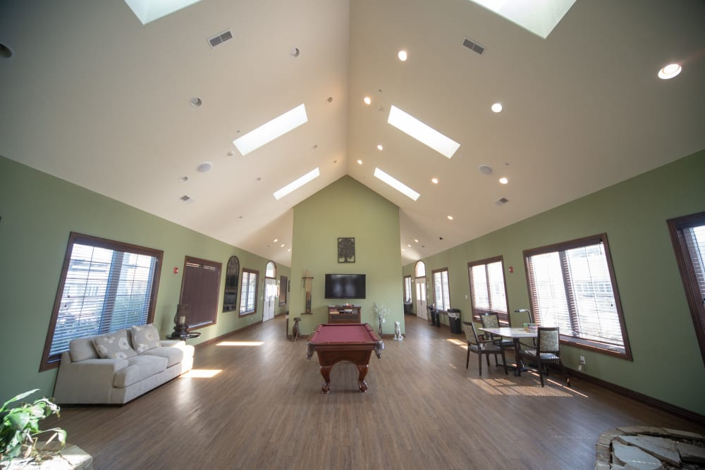 Community lounge with ample seating and a pool table at Villas of Holly Brook Herrin in Carterville, Illinois