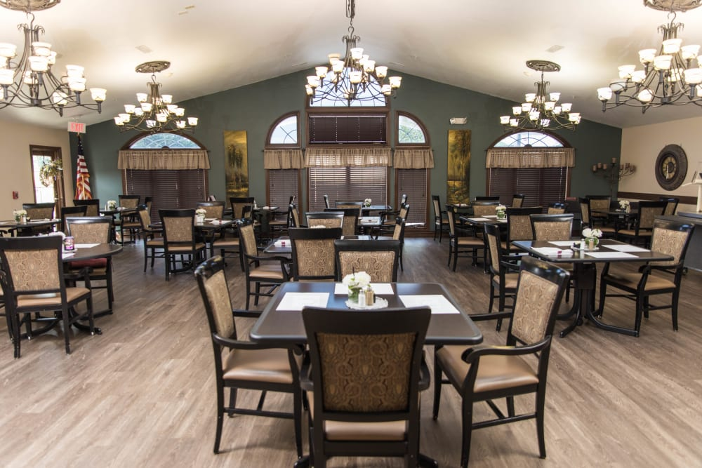 Dining hall with several chandeliers and hardwood flors at Villas of Holly Brook Marshall in Marshall, Illinois