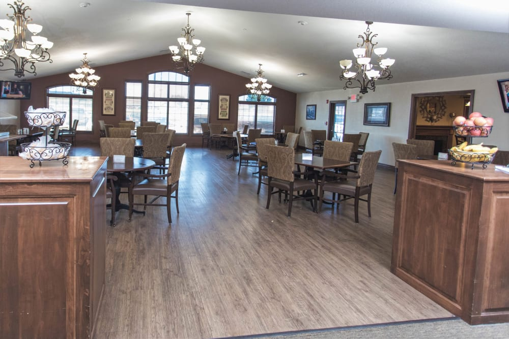 Dining room with hardwood floors and generously spaced out tables at Villas of Holly Brook Shelbyville in Shelbyville, Illinois