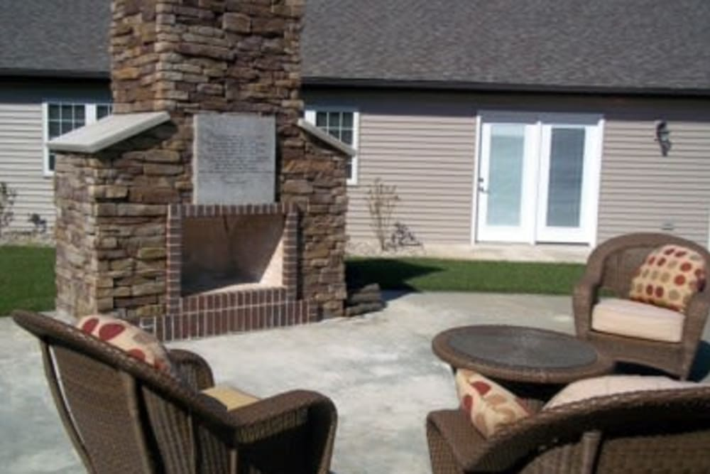 Outdoor patio with a fireplace and seating at Villas of Holly Brook Shelbyville in Shelbyville, Illinois
