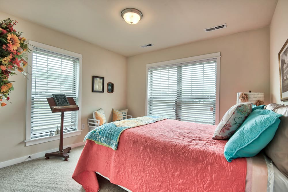 Bedroom model with pink and blue accents at Landings of Oregon in Oregon, Ohio