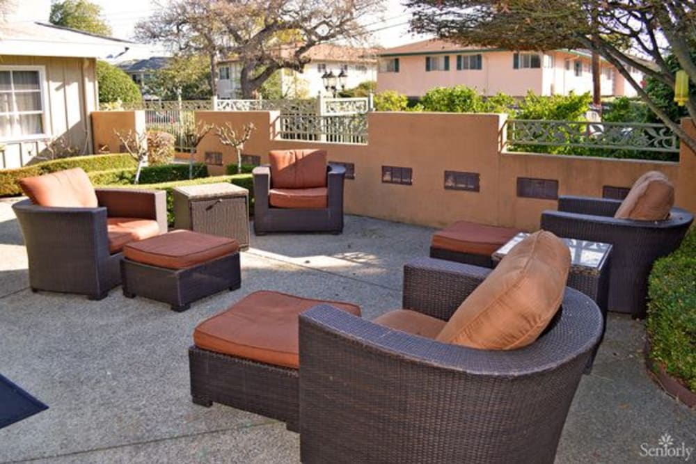 Chairs and footstools outside on the paved patio at Meadow Gardens of Menlo Park in Menlo Park, California