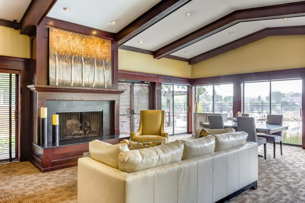The lobby with a fireplace and white couch at Lakeside Apartments in Wheaton, Illinois