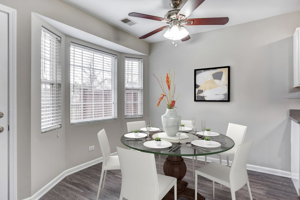 An apartment dining room with ceiling fan and hardwood floors at Lakeview Townhomes at Fox Valley in Aurora, Illinois