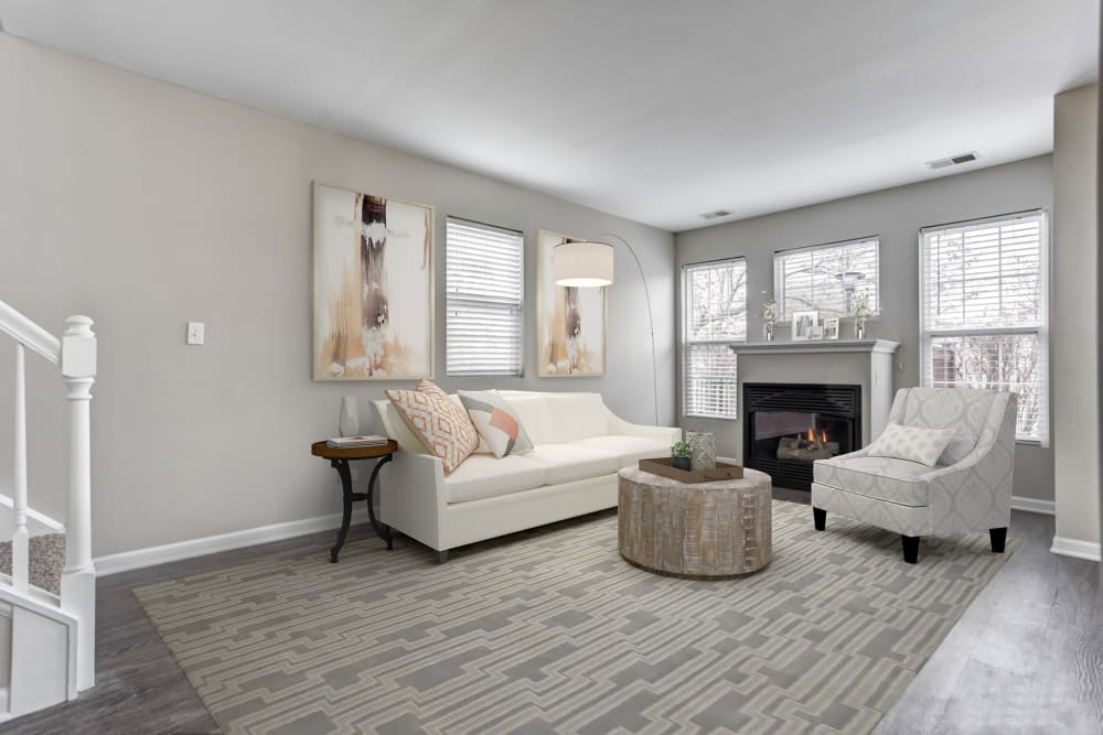 An apartment living room with white furniture, fireplace, and area carpet at Lakeview Townhomes at Fox Valley in Aurora, Illinois