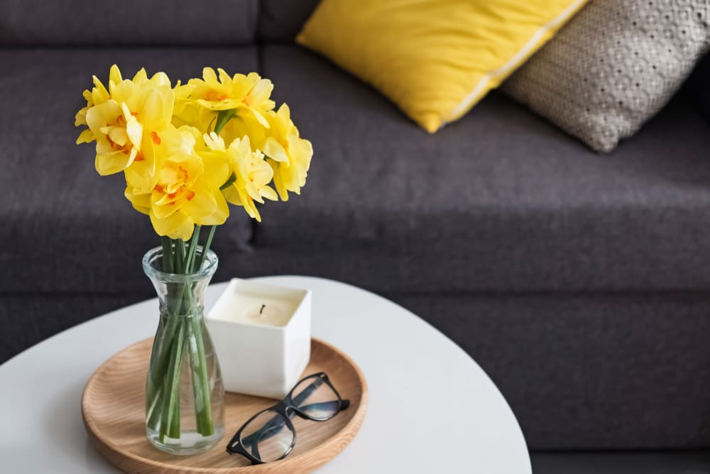 Coffee table with yellow flowers and glasses sitting on top at Bishop's Court in Allouez, Wisconsin