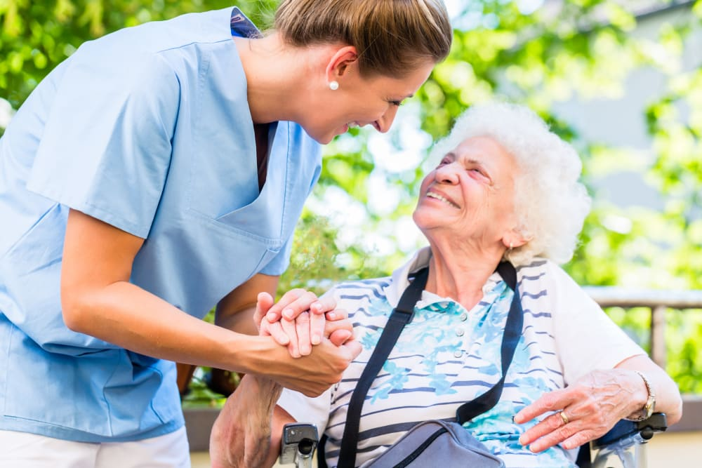 Resident holding hands and looking at a caretaker smiling at Bishop's Court in Allouez, Wisconsin