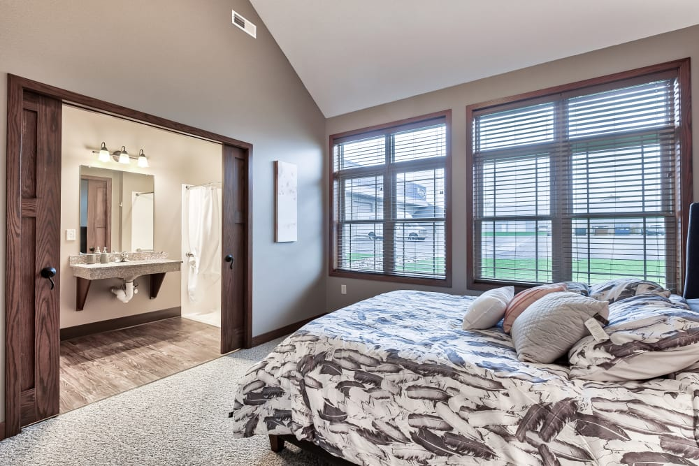 A spacious bedroom with a connected bathroom and large windows to let sunlight in at The Landings of Kaukauna in Kaukauna, Wisconsin