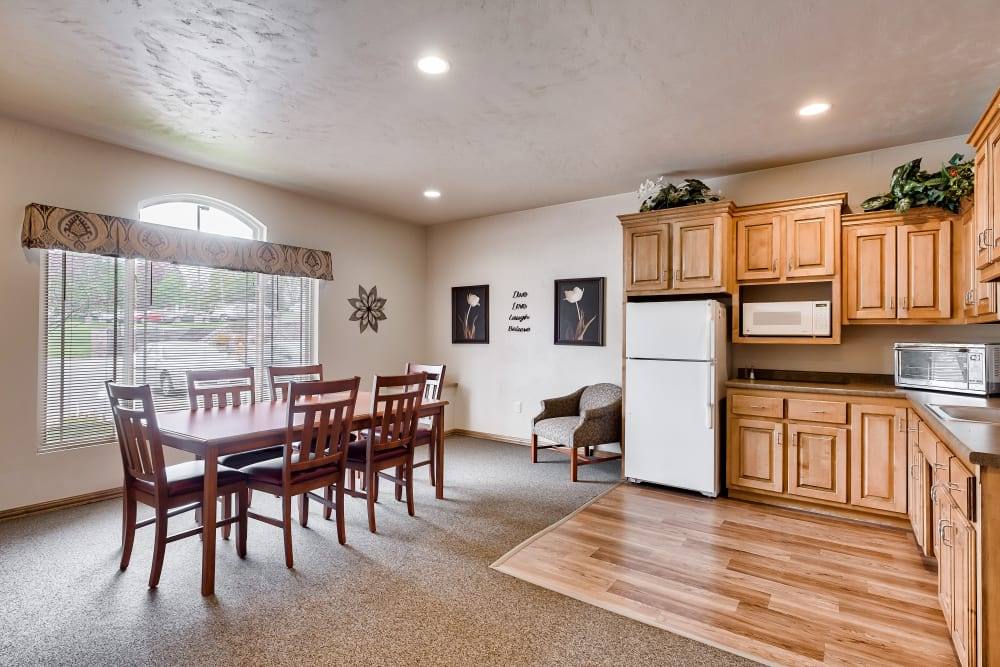 A kitchen and dining area with large windows to let the sunlight in at Allouez Sunrise Village in Green Bay, Wisconsin