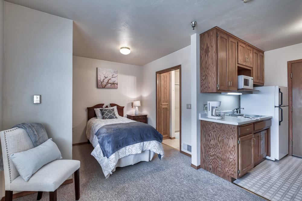 A bedroom and kitchenette at Bishop's Court in Allouez, Wisconsin