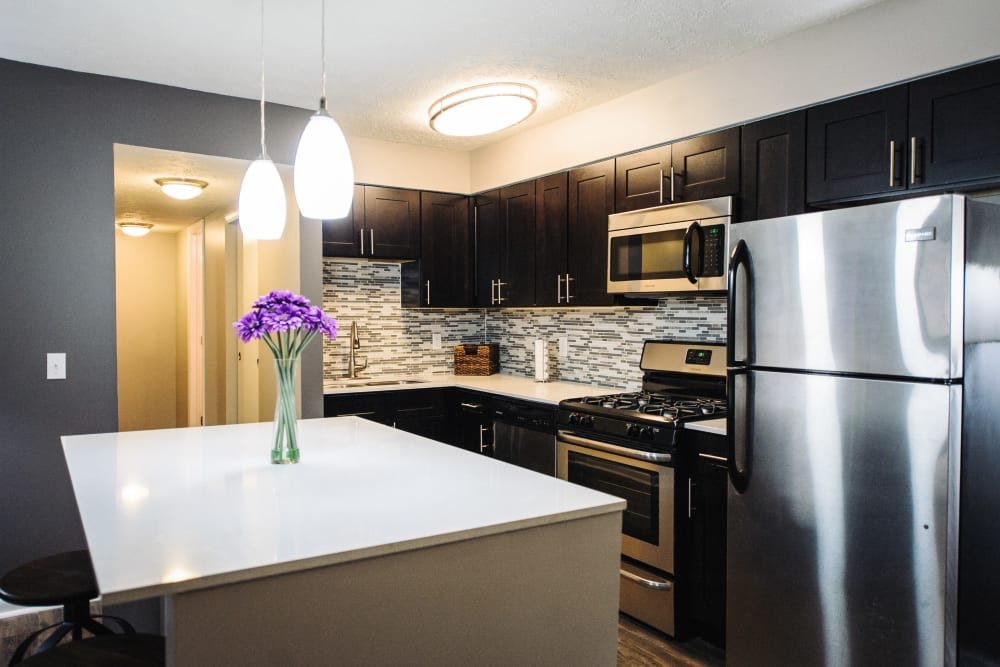 An apartment kitchen with an island at Fox and Hounds Apartments in Columbus, Ohio