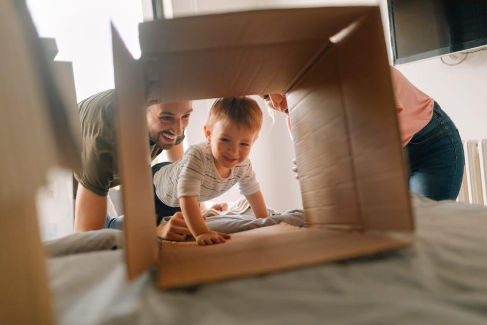 A young child crawling through a box near Hayward Storage LLC in Hayward, California