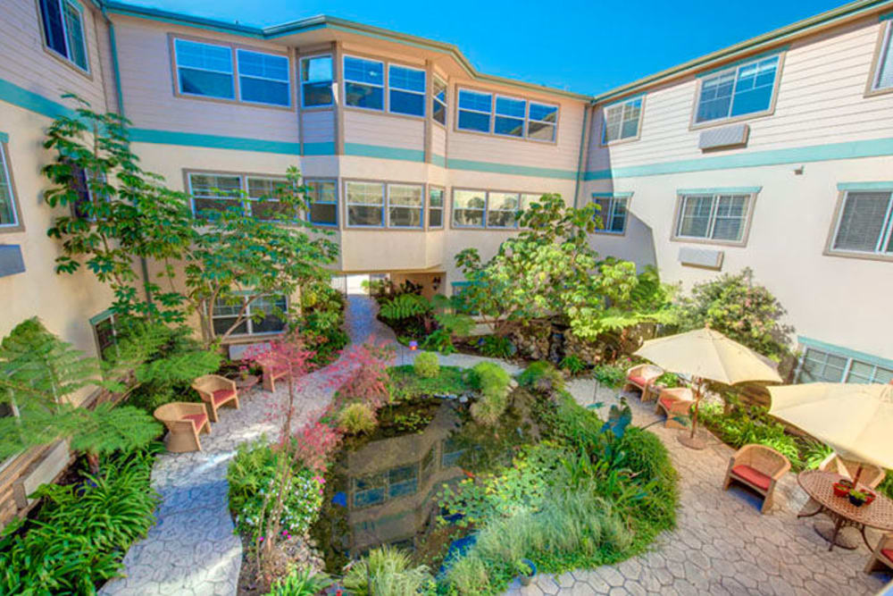 The large central community courtyard with a pond and lots of plantlife at Cypress Place in Ventura, California
