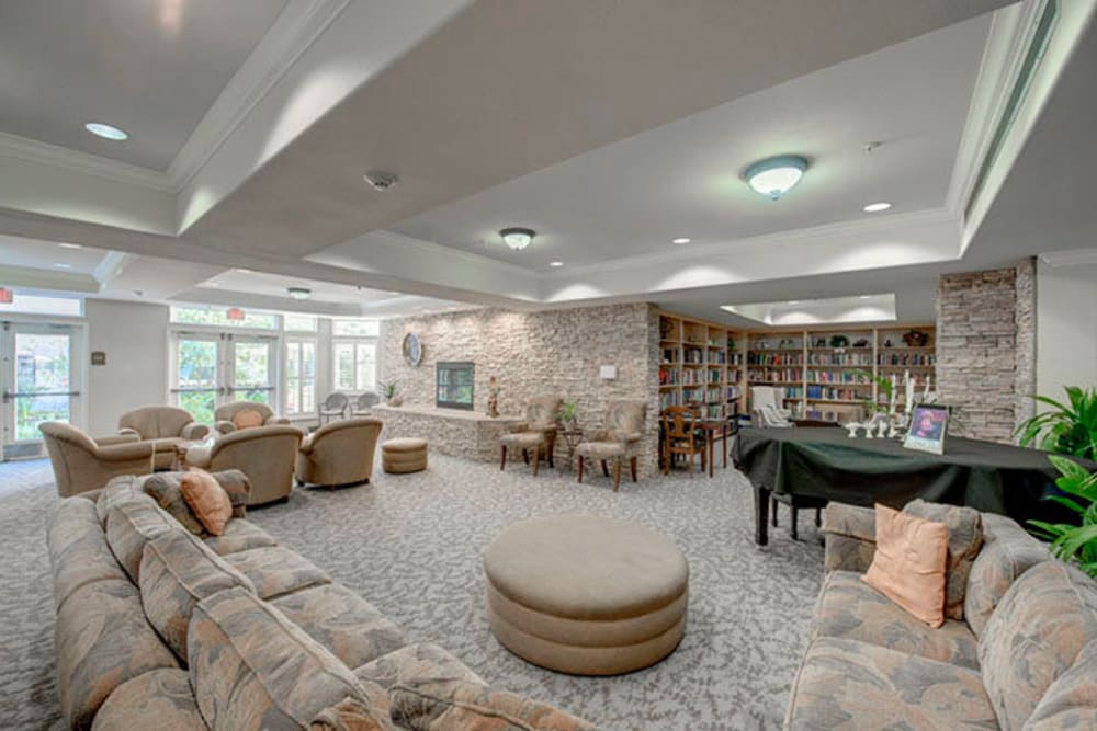 Community lounge with several long couches and access to a library at Cypress Place in Ventura, California