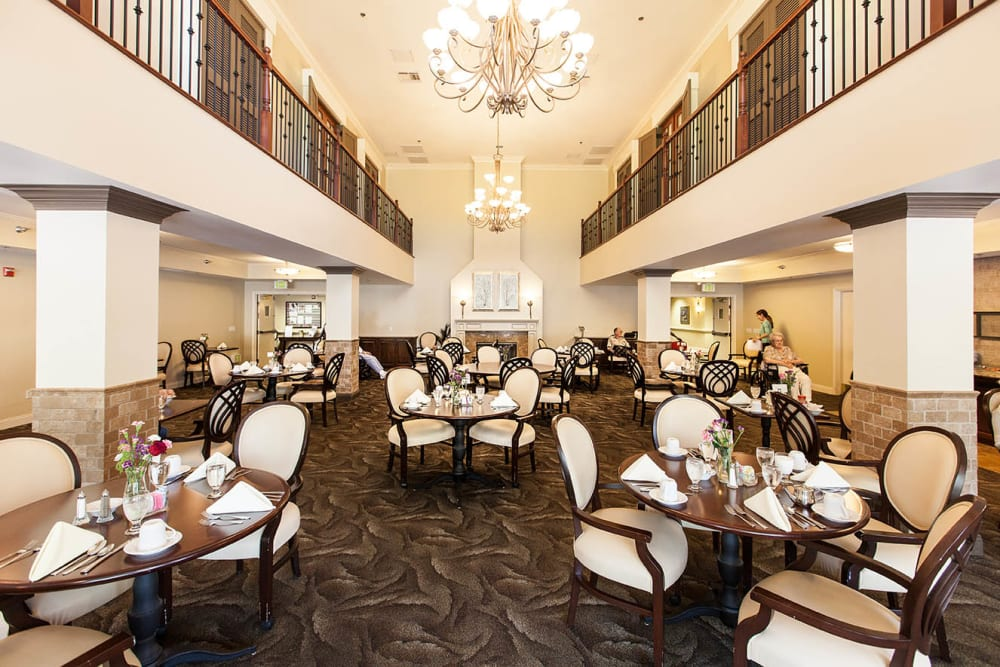 Giant Dining hall with several large chandeliers hanging from the high ceiling at Claremont Place in Claremont, California