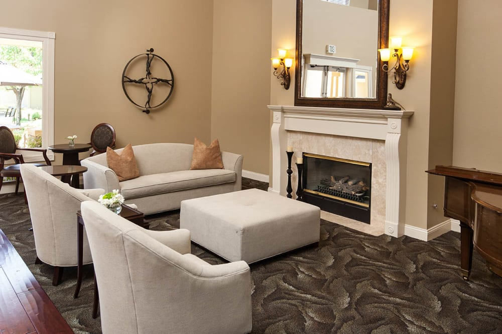 White couches arranges by a fireplace at Claremont Place in Claremont, California