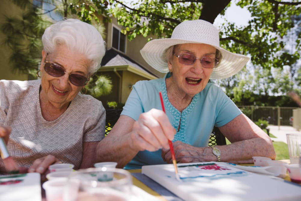2 Residents painting outside at Claremont Place in Claremont, California