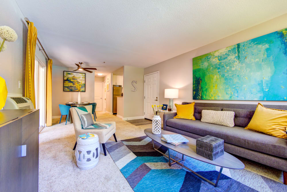Spacious open-concept living area with plush carpeting in a model home at Sofi Sunnyvale in Sunnyvale, California